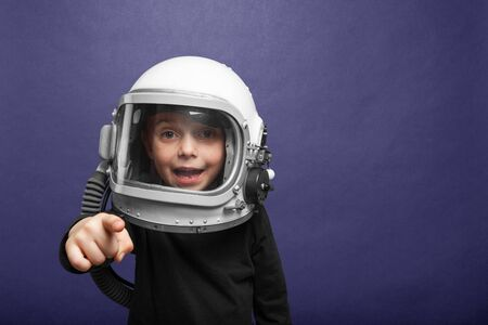 Small child wants to fly an in space wearing an astronaut helmet, on Phantom Blue background