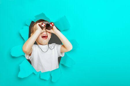 Happy cute boy is having looking through binoculars through a torn hole in yellow paper 免版税图像