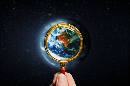 man holds a magnifier on a earth Stock fotó