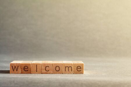 online business inscription engraved on blocks that hold fingers on a gray background. welcome