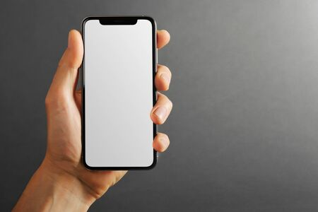 cellphone phone tablet in hand for advertisement on the gray backgrounds 版權商用圖片