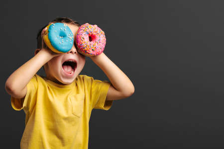 Happy cute boy is having fun played with donuts on black background wall. Bright photo of a boy. Colored donuts Zdjęcie Seryjne