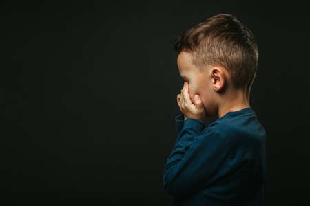 child whose depression is on a black background with his hands closed