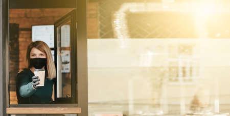 Masked barista spills coffee through the window because of coronavirus