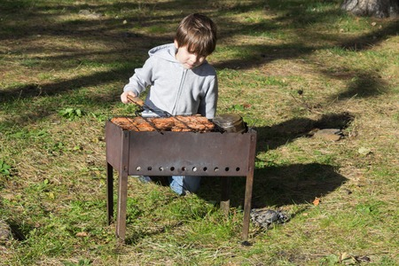 brazier: The boy fries meat on a brazier Stock Photo