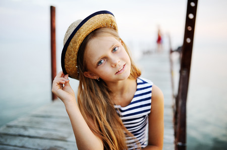 fantasize: little girl on sea background. little girl in a hat