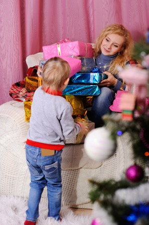 december 25: Mom gives a small child a Christmas gift on the Christmas tree background. Christmas presents