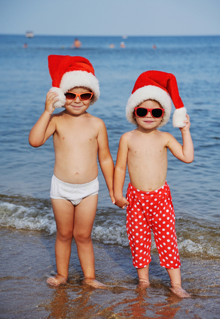 Children in red Santa Claus hats and sunglasses on the background of the sea Stock Photo