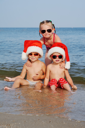 children in Christmas hats and sunglasses frolic in the sea Stock Photo