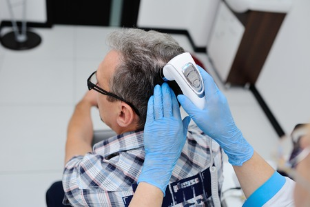 diagnostics hair and scalp. Trihoskopiya. Doctor examine patient male hair a special apparatus