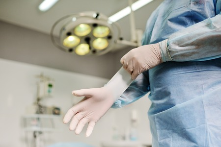 rubber gloves: Surgeon putting on sterile rubber gloves to complicated surgical operation on the background lights. Surgery
