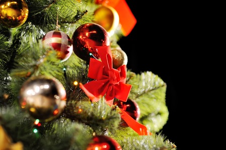 december 25: Christmas background with Christmas tree, Christmas ornaments and a big red bow