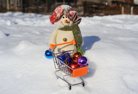 Snowman with a small supermarket trolley and gifts in snow