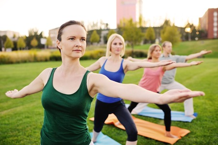 yoga group conducts training outdoors on a background of grass and sunset
