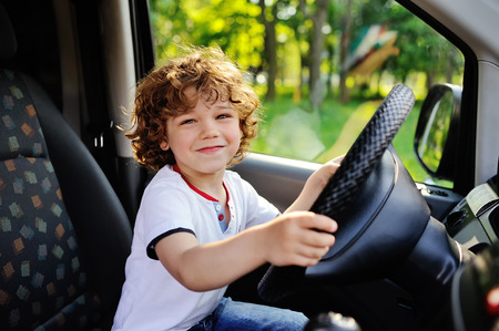 drivers seat: baby boy with curly hair smiling behind the wheel of a car Stock Photo