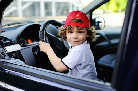 child with curly hair and a red cap sits behind the wheel of a car. baby boy grimaces in car window Standard-Bild