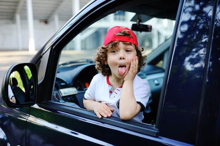 child with curly hair and a red cap sits behind the wheel of a car. baby boy grimaces in car window Stock Photo
