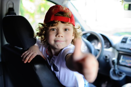child with curly hair and a red cap sits behind the wheel of a car. baby boy grimaces in car window Archivio Fotografico