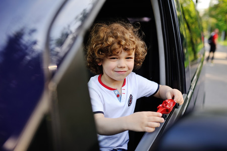 baby boy with curly hair looks out the car window and holding a red toy machine