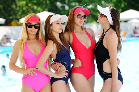Four girl friends in colored closed swimsuits, caps and sunglasses on the background of the pool