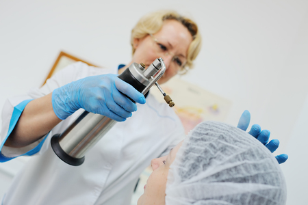 Doctor makes the patient cryotherapy procedure - Cryomassage - cold treatment