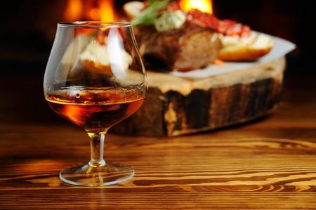 肉料理、暖炉のクローズ アップの背景にコニャックのガラス 写真素材