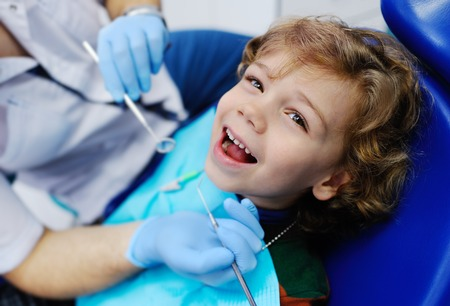 cute child with curly hair in a dental chair smiling