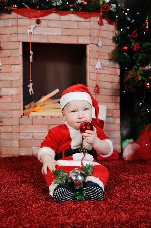teething: Child dressed as Santa Claus Christmas toy chewing teeth. Child in a Santa suit on a background of a brick fireplace. Stock Photo