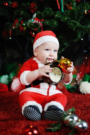 Niño vestido como Santa Claus dientes mordientes reloj despertador. Niño vestido como Santa que se sienta en el fondo del árbol de navidad