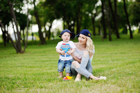 Mother and young son in caps playing in the park on the grass Stock Photo