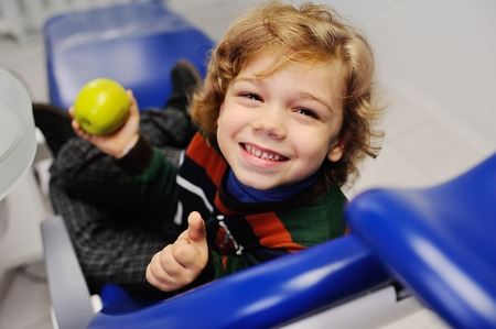 curly-haired child in the dental office smiling and holding a green apple Stock Photo