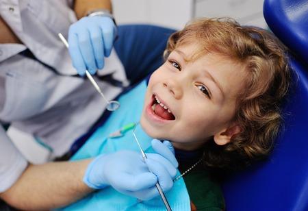 Bebé con el pelo rizado de color rojo en la silla dental azul. dentista de los niños