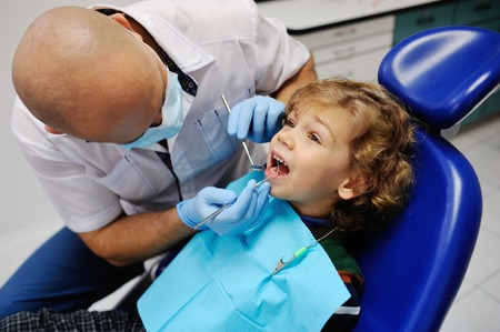 children's dentist examines the mouth baby boy with curly hair Standard-Bild