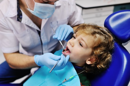 Male dentist examines the teeth of the patient cheerful child with curly red hair. Moloi boy smiling in dentist's chair. child mouth wide open in the dentist's chair