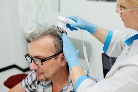 moles: diagnostics hair and scalp. Trihoskopiya. Doctor examine patient male hair a special apparatus
