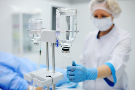 nurse puts the patient medical drip into a vein on the background of the operating room. Dropper against the background of the doctor