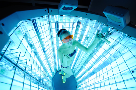 pretty girl on the background of the device for the treatment of light. phototherapy Zdjęcie Seryjne