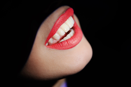 whiten: beautiful teeth on a dark background. mouth woman patient at a reception at the dentist Stock Photo