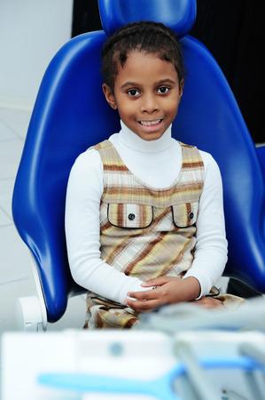 baby girl with dark skin in blue dental chair