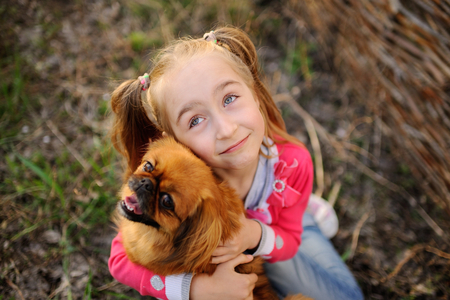 Child playing with dog on grass background Stock Photo