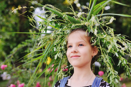 Baby girl in wreath of wild flowers and background of nature. Midsummer. Easter. Ivan Kupala