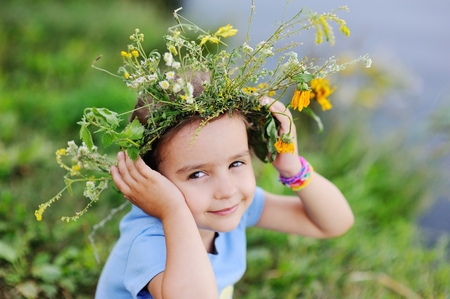 small world: Child girl in a wreath of wild flowers on a background of a river and fresh green grass. Midsummer day. Celebration of the holiday of Ivan Kupala