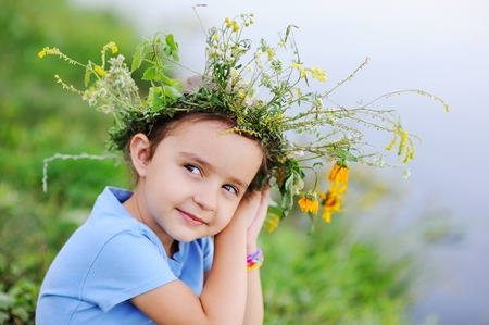 Child girl in a wreath of wild flowers on a background of a river and fresh green grass. Midsummer day. Celebration of the holiday of Ivan Kupala