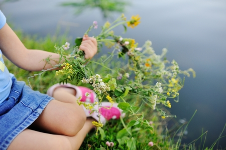 slavs: Child girl lets on the river a wreath of wild flowers. Celebration of Ivan Kupala. Midsummer day