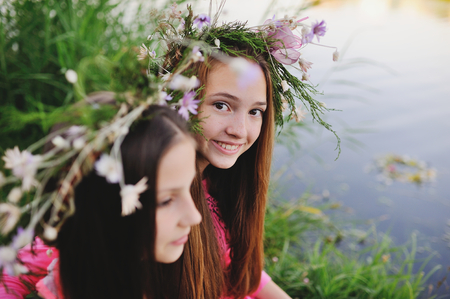 slavs: Two young girls girlfriends in wreaths of field flowers hug on the background of the river