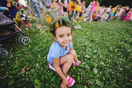 Little girl in a wreath of flowers on a background of people. The celebration of Ivan Kupala