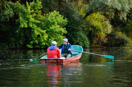 Two fishermen in a red boat with oars with fishing rods catching fish on the background of the river and nature Stock Photo