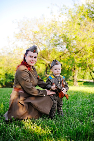 A small son with his mother in the uniform of a Soviet soldier against the background of nature. May 9, Victory Day, World War II, family, peace, against fascism. Stock Photo