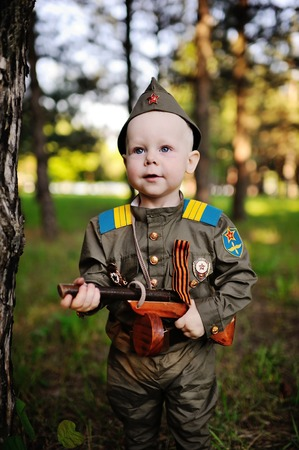 A cute child in the uniform of a Soviet soldier with a St. George ribbon with a toy gun on the background of nature. May 9, February 23, defender, against fascism.