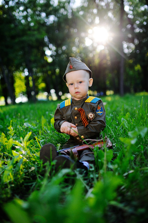 The child in military uniform with a ribbon of siege sits in the grass against the sunset. May 9, Victory Day, February 23, Stock Photo